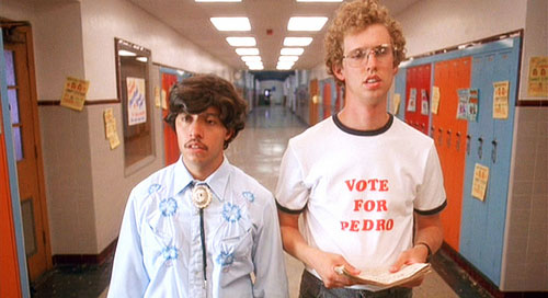 "The movie ""Napoleon Dynamite"", directed by Jared Hess, written by Jared Hess and Jerusha Hess. Seen here from left, Efren Ramirez as Pedro and Jon Heder as Napoleon Dynamite wearing a 'Vote for Pedro' t-shirt. Initial theatrical (limited) release June 11, 2004. Screen capture. © 2004 Twentieth Century Fox. Credit: © 2004 Twentieth Century Fox / Flickr / Courtesy Pikturz. Image intended only for use to help promote the film, in an editorial, non-commercial context."